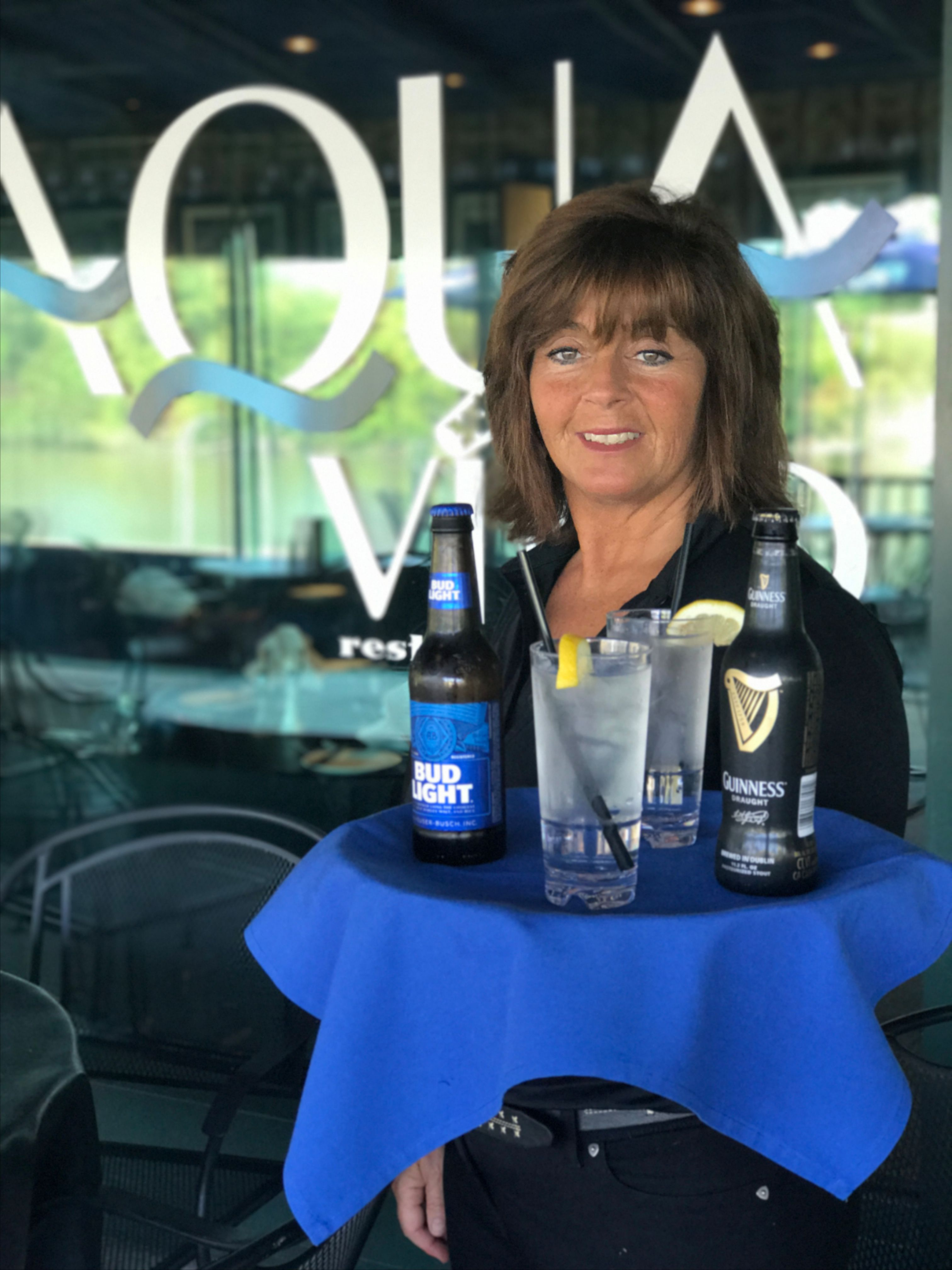 trish holding tray of beer bottles and glasses filled with water